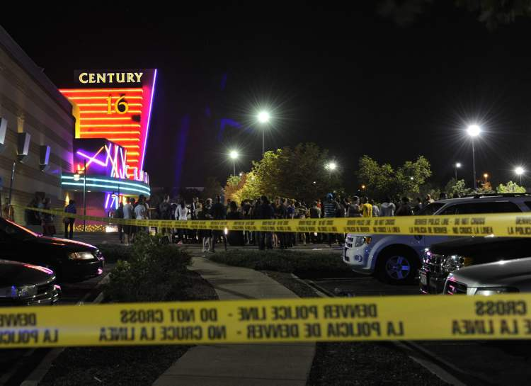 People gather outside the Century 16 movie theatre in Aurora, Colo., at the scene of a mass shooting early Friday morning, July 20, 2012. Police Chief Dan Oates says 14 people are dead following the shooting at the suburban Denver movie theater. He says 50 others were injured when gunfire erupted early Friday at the Aurora theater. Oates says a gunman appeared at the front of one of the Century 16 theaters. (AP Photo/The Denver Post, Karl Gehring) (CP)