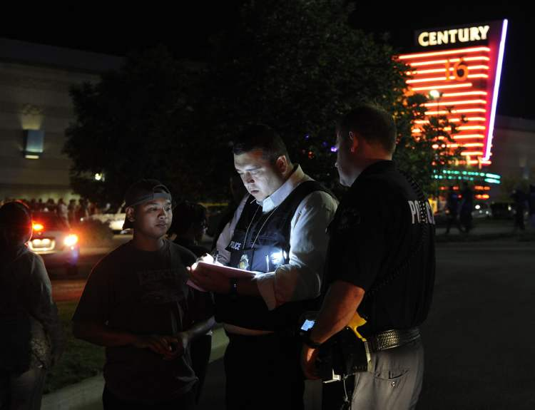 An Aurora Police Department detective takes a witness statement following a shooting Friday morning July 20, 2012. Aurora Police responded to the Century 16 movie theatre early Friday morning where police confirm at least 14 people are dead and 50 others injured. (AP Photo/Karl Gehring, The Denver Post) (CP)