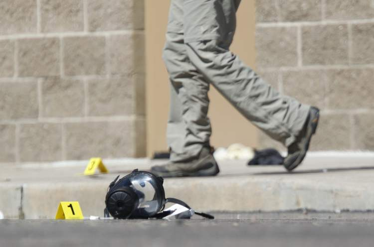 Yellow markers sit next to evidence, including a gas mask, as police investigate the scene outside the Century 16 movie theater east of the Aurora Mall in Aurora, Colo. on Friday, July 20, 2012. A gunman in a gas mask barged into a crowded Denver-area theater during a midnight showing of the Batman movie on Friday, hurled a gas canister and then opened fire in one of the deadliest mass shootings in recent U.S. history. (AP Photo/David Zalubowski) (CP)