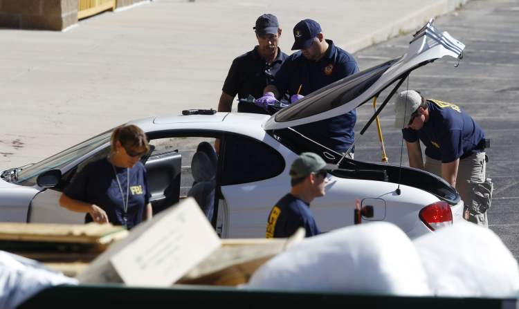 Investigators examine a vehicle parked outside a back exit at the Century 16 movie theater east of the Aurora Mall in Aurora, Colo. on Friday, July 20, 2012. A gunman in a gas mask barged into a crowded Denver-area theater during a midnight showing of the Batman movie on Friday, hurled a gas canister and then opened fire in one of the deadliest mass shootings in recent U.S. history. (AP Photo/David Zalubowski) (CP)