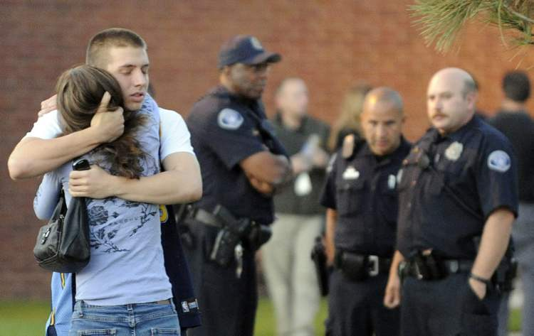 Eyewitness Jacob Stevens, 18, hugs his mother Tammi Stevens after being interview by police outside Gateway High School where witnesses were brought for questioning Friday, July 20, 2012 in Aurora, Colo. A gunman wearing a gas mask set off an unknown gas and fired into the crowded movie theater killing 12 people and injuring at least 50 others, authorities said. (AP Photo/The Denver Post, RJ Sangosti) TV, INTERNET AND MAGAZINES CALL FOR RATES AND TERMS