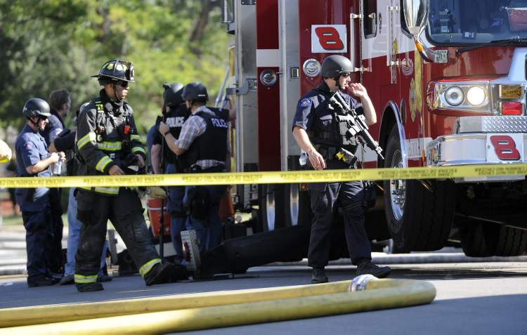 Law enforcement officials gather behind a fire truck as they search the home where the suspect in a shooting at a movie theatre lived in Aurora, Colo., Friday, July 20, 2012. A gunman wearing a gas mask set off an unknown gas and fired into the crowded movie theater killing 12 people and injuring at least 50 others, authorities said. (AP Photo/The Denver Post, Cyrus McCrimmon) TV, INTERNET AND MAGAZINES CALL FOR RATES AND TERMS (CP)