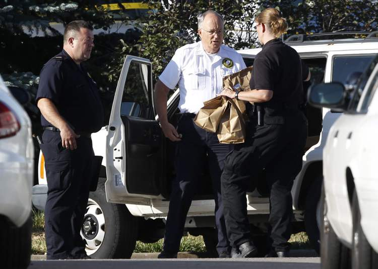 "Officers load bags of evidence into a car outside the Century 16 theater east of the Aurora Mall in Aurora, Colo., on Friday, July 20, 2012. A shooting took place in the theater in which at least 12 people died and scores were injured during the premiere showing of ""The Dark Knight Rises."" (AP Photo/David Zalubowski) (CP)"