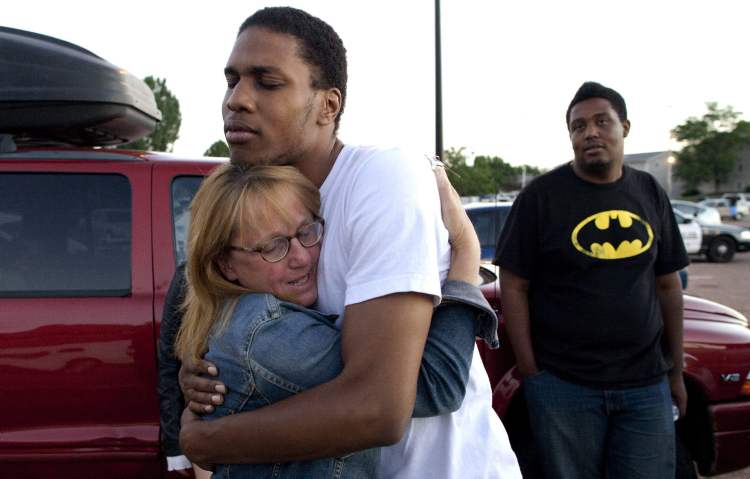 Judy Goos, left, hugs her daughters friend, Isaiah Bow, 20, an eyewitnesses, as Terrell Wallin, 20, right, looks on, outside Gateway High School where witnesses were brought for questioning after a gunman opened fire at the midnight premiere of the