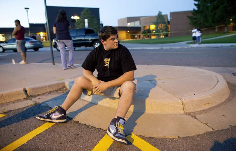 Eyewitness Chandler Brannon, 25, sits outside Gateway High School where witnesses were brought for questioning after a shooting at a movie theater showing the Batman movie