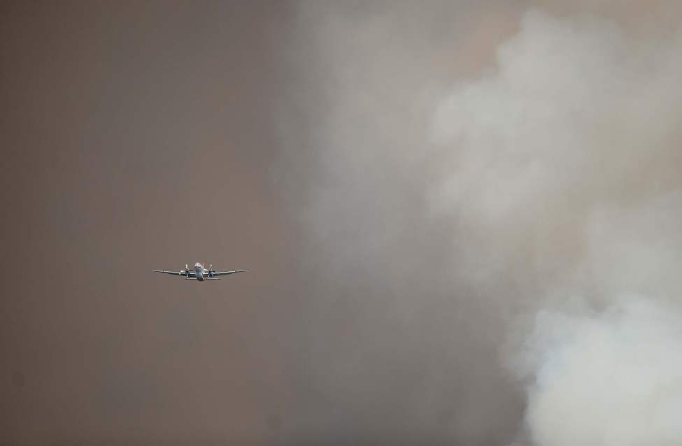 A slurry plane flies through the dark smoke west of Manitou Springs, Colorado, Sunday, June 24, 2012, as the Waldo Canyon Fire grows on the second day. (Christian Murdock/Colorado Springs Gazette/MCT)