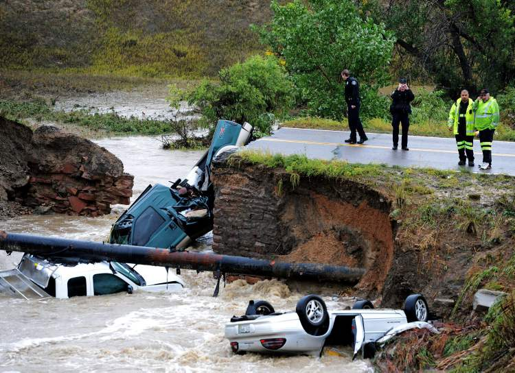 Officials investigate the scene of a road collapse at Highway 287 and Dillon at the Broomfield/Lafayette border, Colo., that sent three vehicles into the water after flash flooding on Thursday.