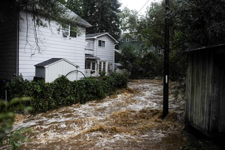 Floodwaters rush down Cheyenne Creek as storms continue to hit Colorado Springs, Colo., Friday.