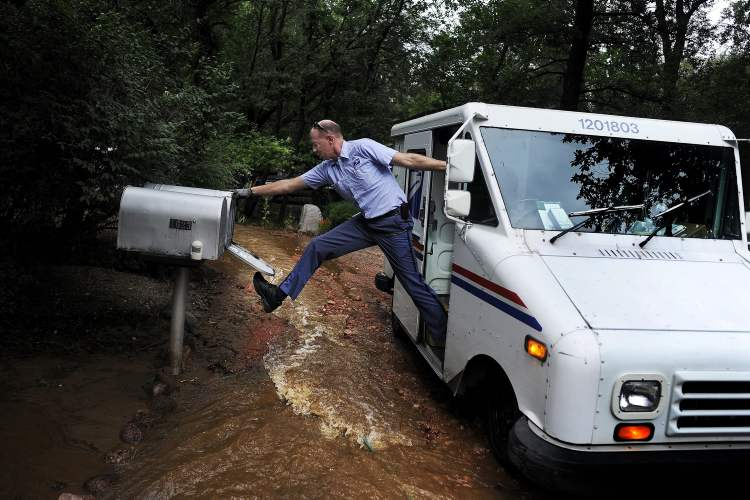 Dave Jackson closes a mailbox with his foot after delivering the mail to a home surrounded on three sides by a flooded Cheyenne Creek in Colorado Springs, Colo. Friday. (Michael Ciaglo / Colorado Springs Gazette / MCT)