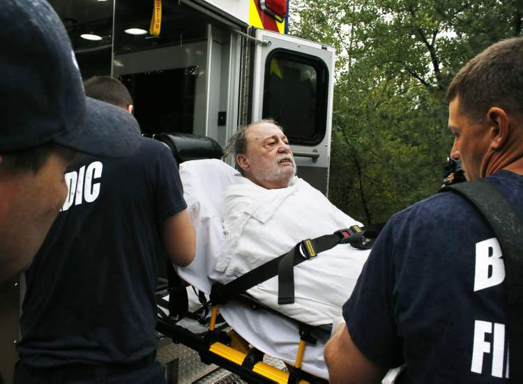 Will Pitner is rescued by emergency workers Friday after a night trapped sheltering outside on high ground above his home as it filled with water after days of record rain and flooding, at the base of Boulder Canyon, Colo. People in Boulder were ordered to evacuate as water rose to dangerous levels amid a storm system that has been dropping rain for a week. Rescuers struggled to reach dozens of people cut off by flooding in mountain communities, while residents in the Denver area and other areas were warned to stay off flooded streets. (Brennan Linsley / The Associated Press)