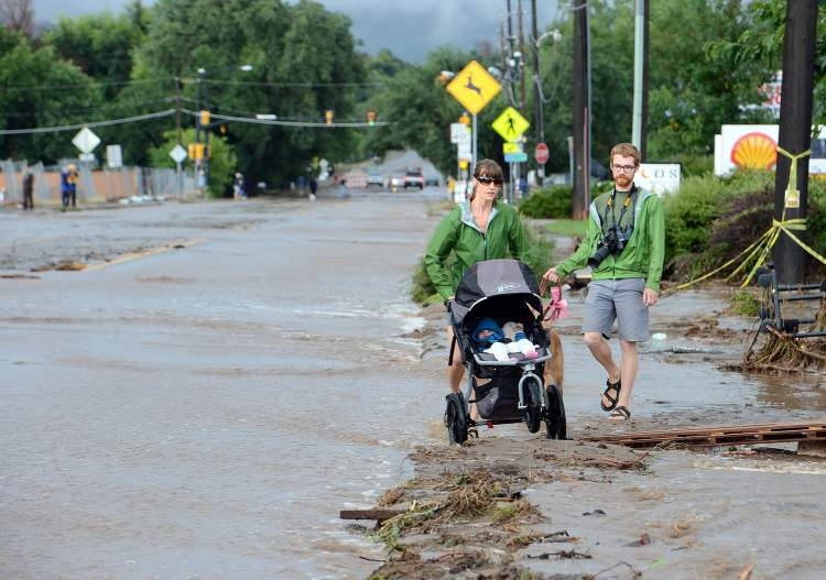 Kimberly Meyers, her husband, Traeger, and baby Harper, walk along North Broadway in Boulder, Colo., to survey the flood damage on Friday.