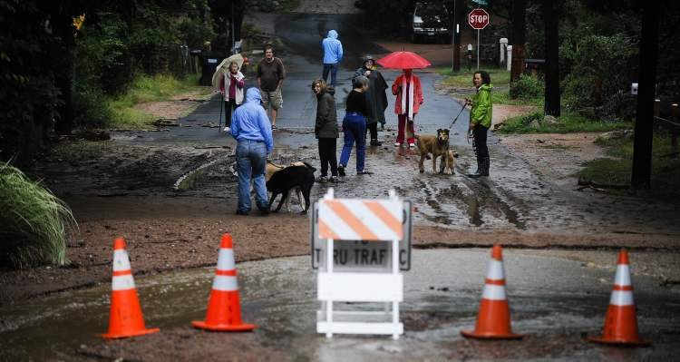 Residents check out the closed bridge on Stratton Avenue as water continues to rush down Cheyenne Creek in Colorado Springs, Colo., Friday. (Michael Ciaglo / Colorado Springs Gazette / MCT)