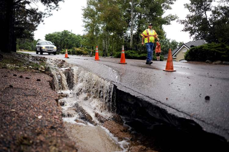 Colorado Springs Utilities workers inspect a 30-foot section of Old Stage Road near Pine Road that washed out as water floods the area in Colorado Springs, Colo., Friday.