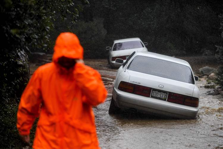 Cars sit in a flooded driveway as Cheyenne Creek flows over its banks and into the surrounding creek-side properties in Colorado Springs, Colo., Friday.