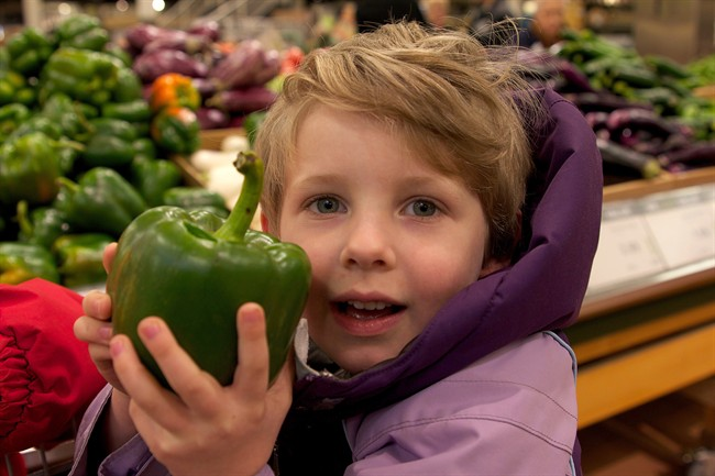 A child holds up a green pepper in this undated photo. Grocery shopping can be a great way to teach your kids about making healthy choices and help them learn a life skill, say Dietitians of Canada. THE CANADIAN PRESS/HO, Dietitians of Canada