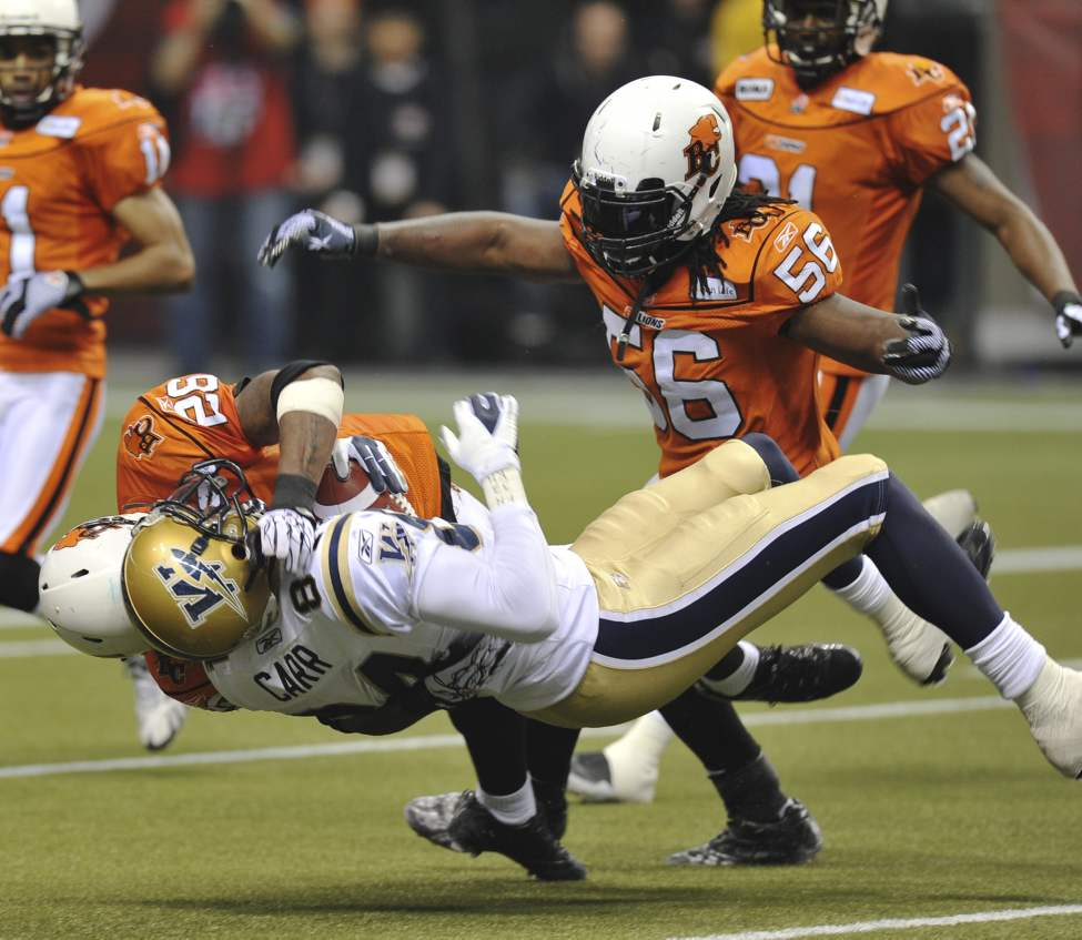 Winnipeg Blue Bomber Greg Carr is tackled by B.C. Lions Anthony Reddick as Lions Solomon Elimimian (#56) steps in during first-half action.   (Jason Payne / Postmedia News)