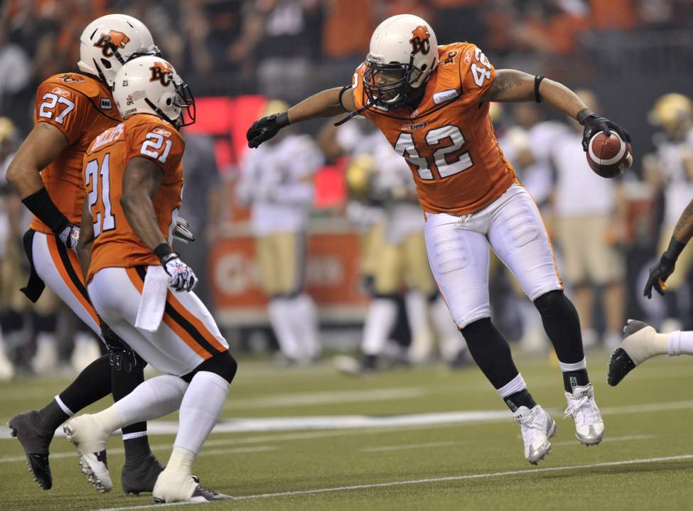 B.C. Lions linebacker Anton McKenzie, right, celebrates a pass interception with teammates J.R. LaRose left, and Ryan Phillips during first-quarter action.