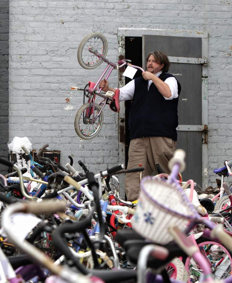 Nathan Wild a volunteer with The Wrench brings a fixed bicycle out to the storage yard during the Cycle of Giving at the Atomic Centre on Logan Avenue.  Mike Deal / Winnipeg Free Press
