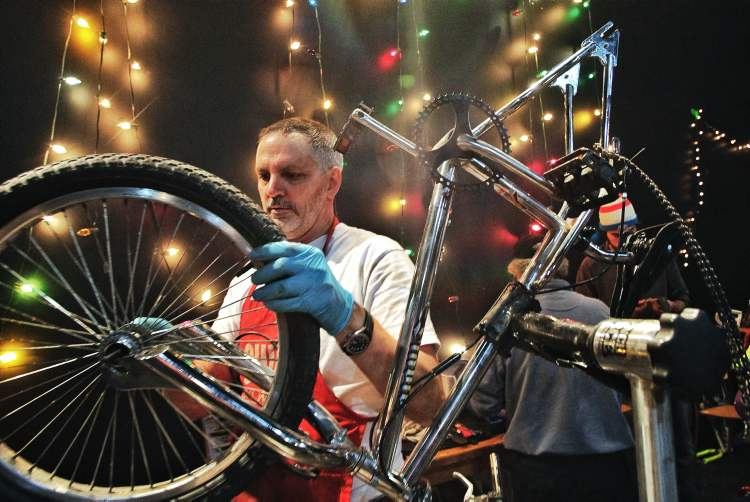 Jason Carter the past president of the Manitoba Cycling Association works on a bike during the Cycle of Giving at the Atomic Centre on Logan Avenue.  Mike Deal / Winnipeg Free Press