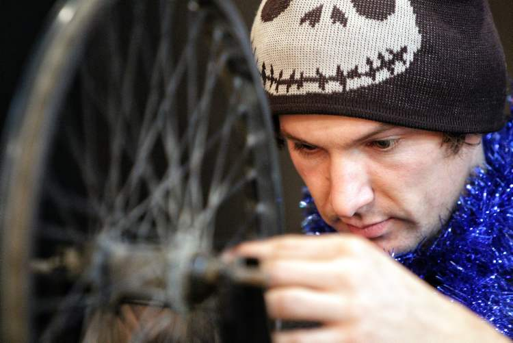 Geoff Heath the mechanical director at The Wrench, a bicycle repair education and cycling hub, works on fixing some spokes during the Cycle of Giving at the Atomic Centre on Logan Avenue. 