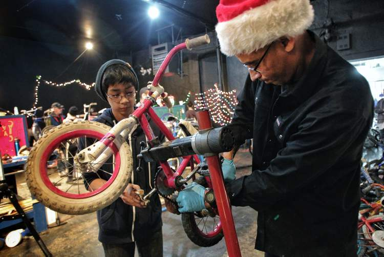 Seth Belmore (left), 12, and Dave Dorning the coordinator of the University of Winnipeg Students Association Bike Lab work on a bike together during the Cycle of Giving at the Atomic Centre on Logan Avenue. 