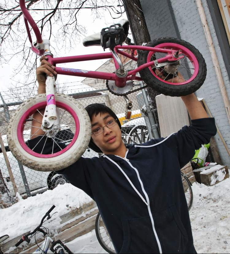 Seth Belmore (left), 12, of the University of Winnipeg Students Association Bike Lab holds up one of the bikes he fixed for a photo his friend Dave Dorning is taking during the Cycle of Giving at the Atomic Centre on Logan Avenue. 