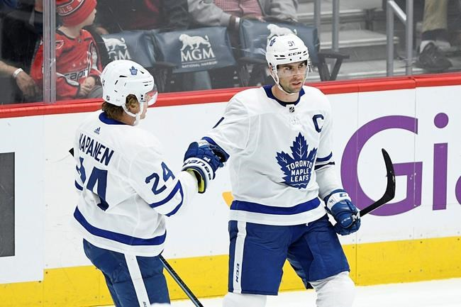 Toronto Maple Leafs center John Tavares, right, celebrates his goal with right wing Kasperi Kapanen (24), of Finland, during the third period of the team's NHL hockey game against the Washington Capitals, Wednesday, Oct. 16, 2019, in Washington. Tavares will be out at least two weeks with a broken finger. THE CANADIAN PRESS/AP/Nick Wass
