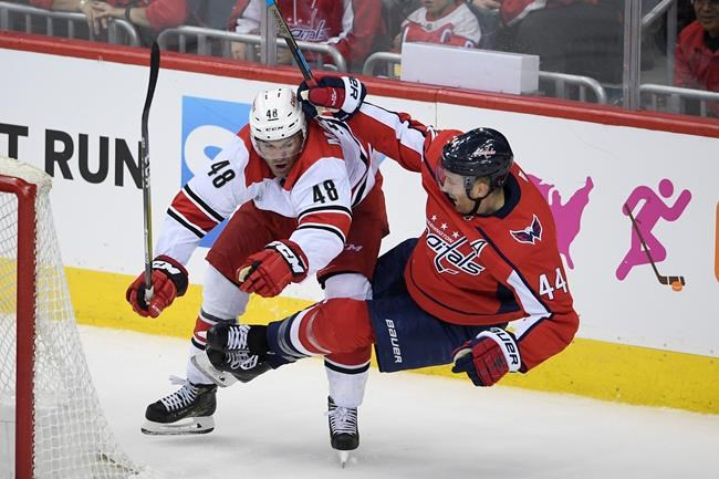 Carolina Hurricanes left wing Jordan Martinook (48) and Washington Capitals defenseman Brooks Orpik (44) work behind the goal during the third period of Game 1 of an NHL hockey first-round playoff series Thursday, April 11, 2019, in Washington. The Capitals won 4-2. (AP Photo/Nick Wass)
