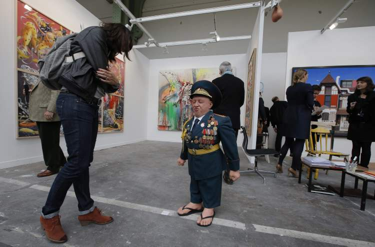 "A woman looks at ""Soviet Suprem 2012"" by artist Gilles Barbier during the opening at Grand Palais of the FIAC, International Contemporary Art Fair, which runs from Oct. 18 to 21, 2012, in Paris, Wednesday, Oct. 17, 2012. (AP Photo/Francois Mori)"
