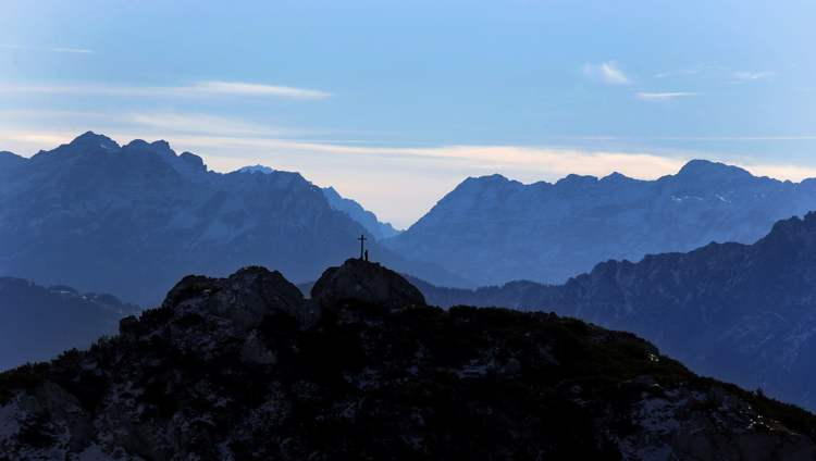 A hiker rests near a cross as he enjoys the view over the Alps near the top of Wendelstein mountain (1,838 meters; 6,030 feet) near Bayrischzell, southern Germany, Wednesday, Oct. 17, 2012. 