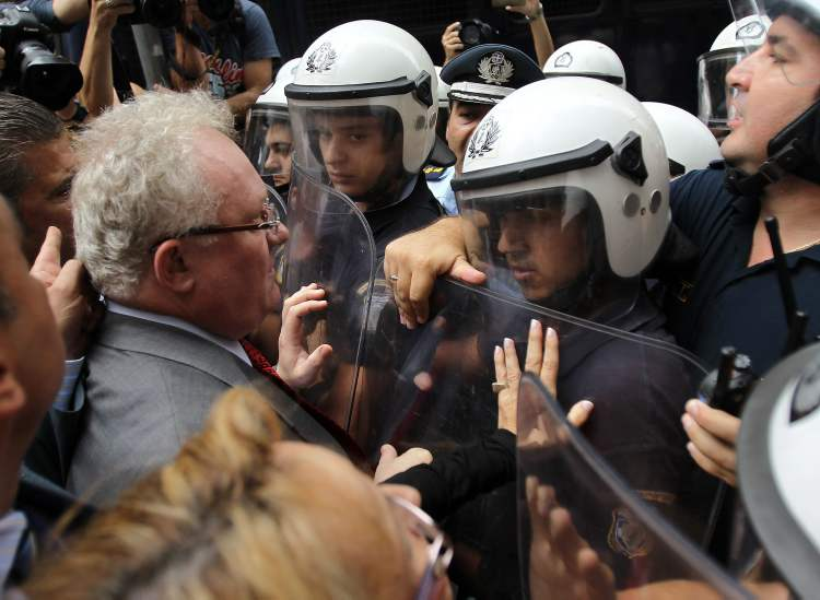 Lawyers and doctors scuffle with riot police during an anti-austerity protest outside the Finance Ministry in Athens, Wednesday, Oct. 17, 2012.
