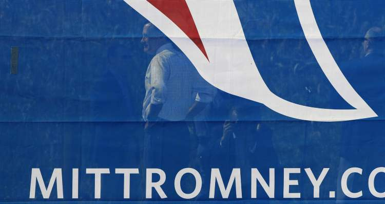 Republican presidential candidate, former Gov. Mitt Romney stands behind a banner as he waits to be introduced during a rally at Tidewater Community college in Chesapeake, Va., Wednesday, Oct. 17, 2012.  (AP Photo / Steve Helber)