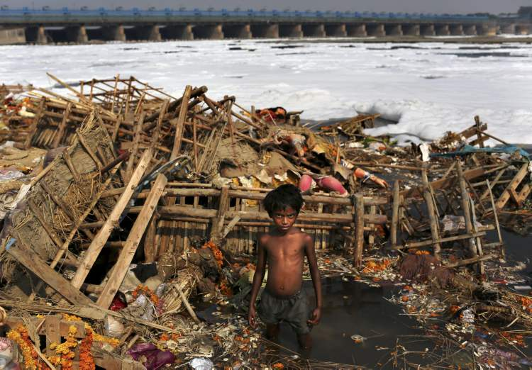 An Indian boy poses as he scavenges amongst the remains of large idols of the Hindu goddess Durga that were immersed by devotees in a polluted section of the Yamuna river the previous day as part of the Durga Puja festival in New Delhi, India, Thursday, Oct. 25, 2012. Thousands of the idols are left by worshippers in the holy river as part of the festival which commemorates the slaying of a demon king by lion-riding, ten armed goddess Durga, marking the triumph of good over evil. (AP Photo/Kevin Frayer)