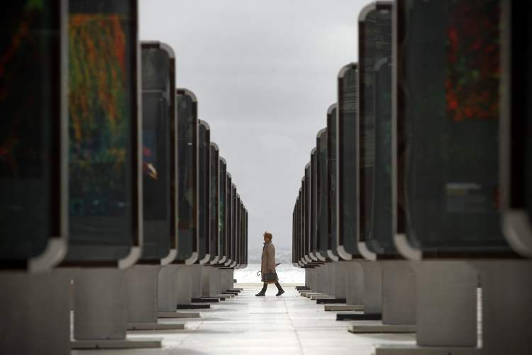 A woman looks at pictures and paintings placed in frames during a street exhibition at Lisbon's Comercio square, Thursday, Oct. 25, 2012. (AP Photo/Francisco Seco)