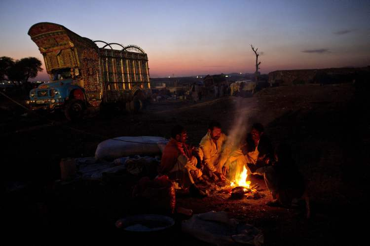 Pakistani vendors sits around a fire to keep themselves warm in a livestock market set up for the upcoming Eid al-Adha festival in Islamabad, Pakistan,Thursday, Oct. 25, 2012. Muslims will celebrate Eid al-Adha, or the Feast of the Sacrifice, on Oct. 27, by slaughtering of sheep, goats, cows or camels. (AP Photo/B.K. Bangash)