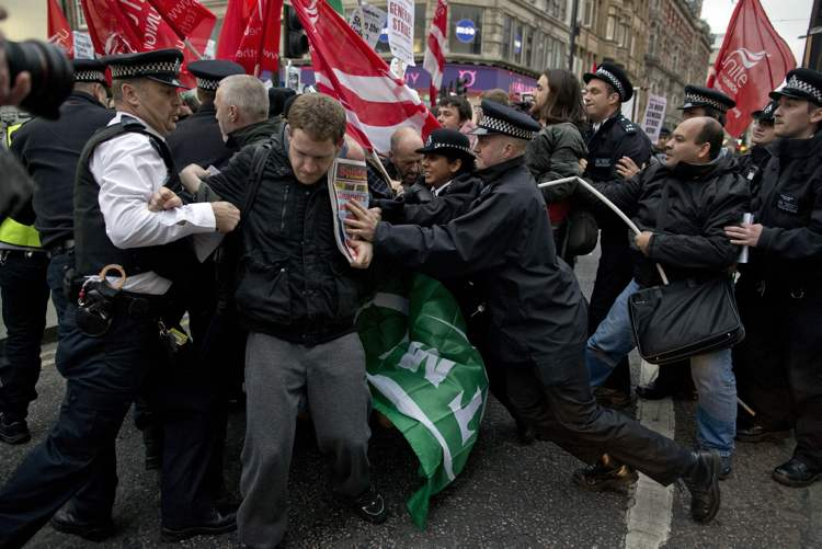 Police officers try to push protesters back onto the pavement after they blocked traffic on Oxford Street, London, whilst taking part in a picket and demonstration they said was over dismissals of 28 workers employed by contractors on the Crossrail transport project, for being trade union members, Wednesday, Nov. 14, 2012. (AP Photo/Matt Dunham)