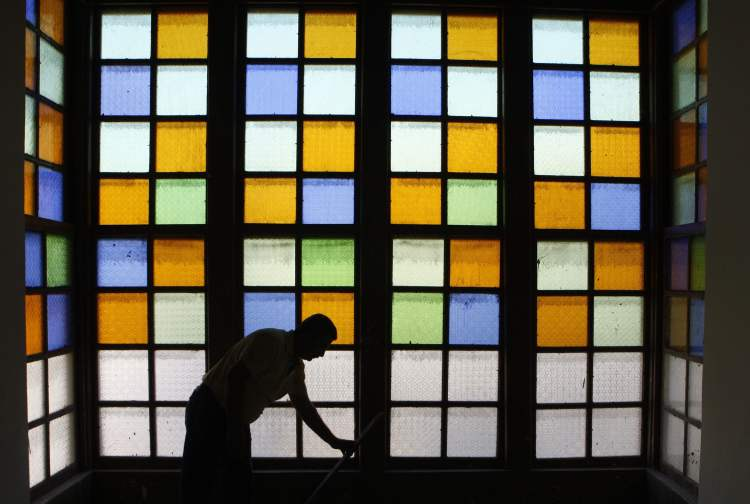 A man cleans the window at an old house used by Khalil Pasha, the last Ottoman governor for Baghdad, in Baghdad, Iraq, Thursday, Nov. 15, 2012. (AP Photo/Karim Kadim)