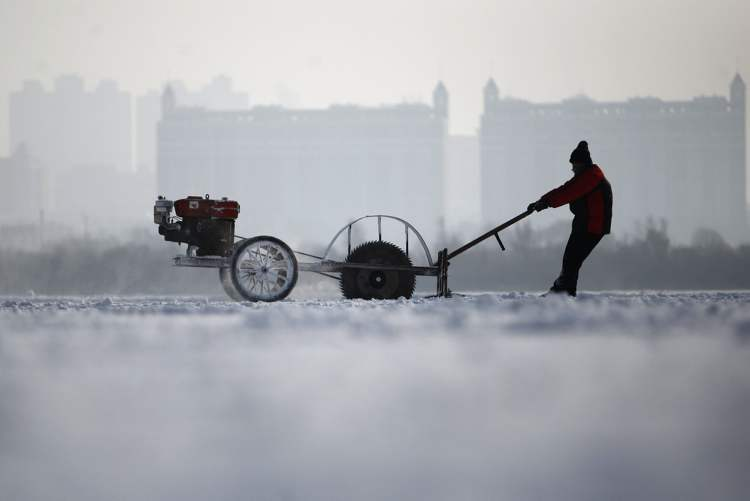 A worker uses a machine to cut ice at the frozen Songhua River in Harbin in northeast China's Heilongjiang province on Tuesday Dec. 4, 2012. The city is preparing for its annual ice festival where large blocks of ice are used to build a tourist attraction. (AP Photo)
