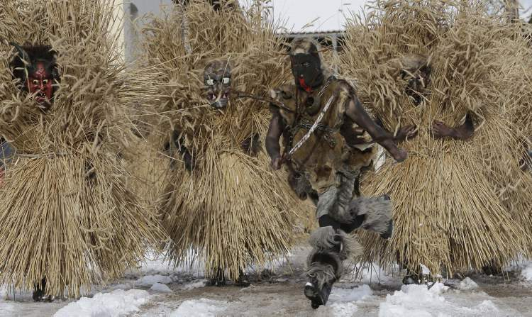 "Men dressed in bizarre straw outfits and devilish masks start the traditional ""Buttnmandl"" run, when they shout and make noise with cowbells to frighten people in the village of Bischofswiesen, Germany, Wednesday, Dec. 5, 2012. The pre-Christmas tradition dates back to pagan times as a protection against evil spirits in the darkest time of the year. (AP Photo/Matthias Schrader)"