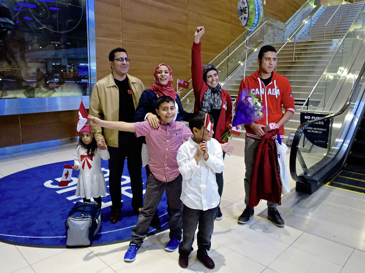 Tiba Al Abdellah (centre with fist raised) is greeted by her family members in Winnipeg (at left) and brother Tarek (at right) after arriving from Lebanon.