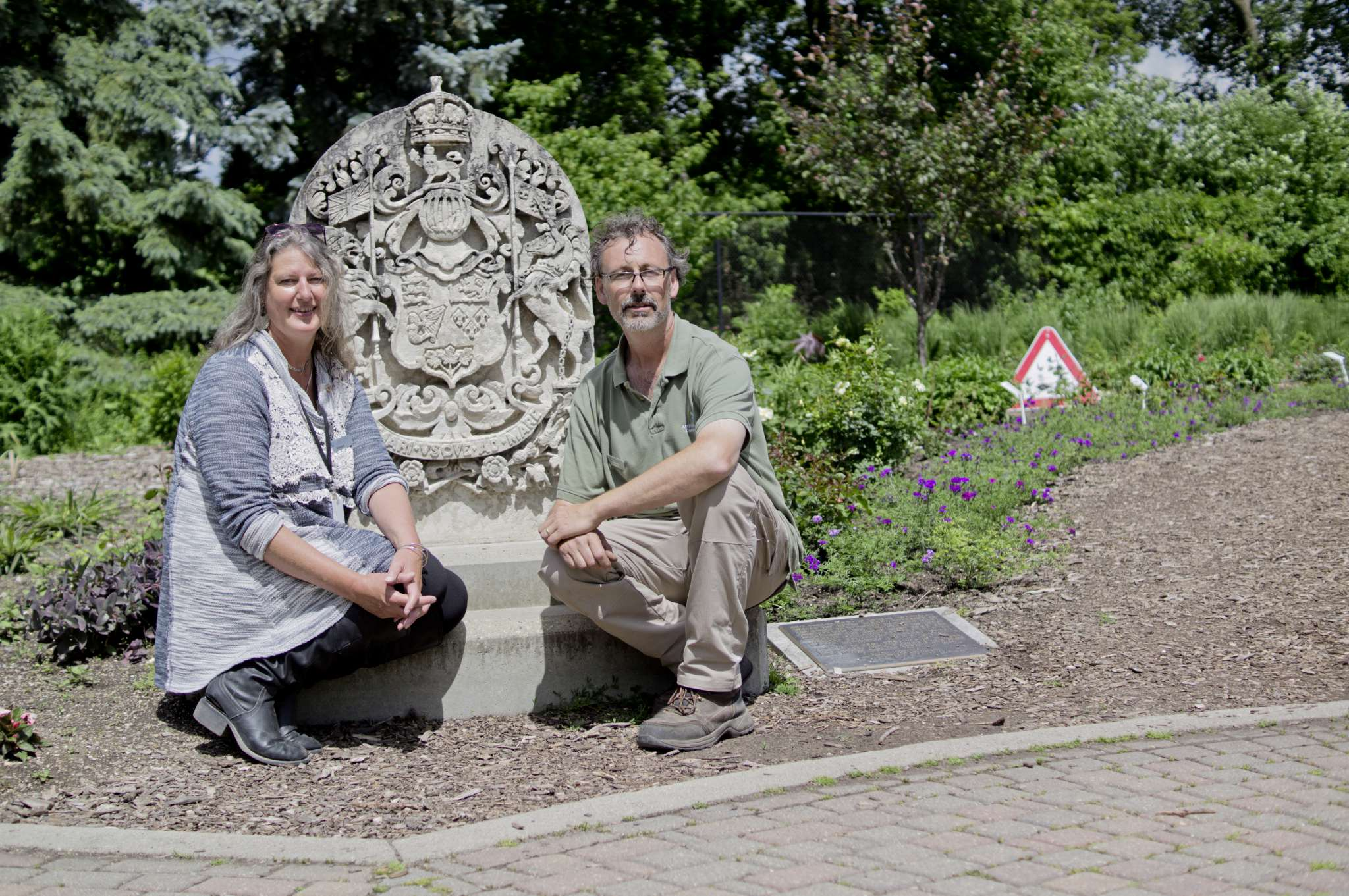 Kaaren Pearce, director of horticulture, and Craig Gillespie, crew lead in the English Garden, at Assiniboine Park pose next to the Canadian coat of arms near the rose garden. Assiniboine Park's gardens were selected as one of the top 150 garden experiences in the country by the Canadian Garden Council.