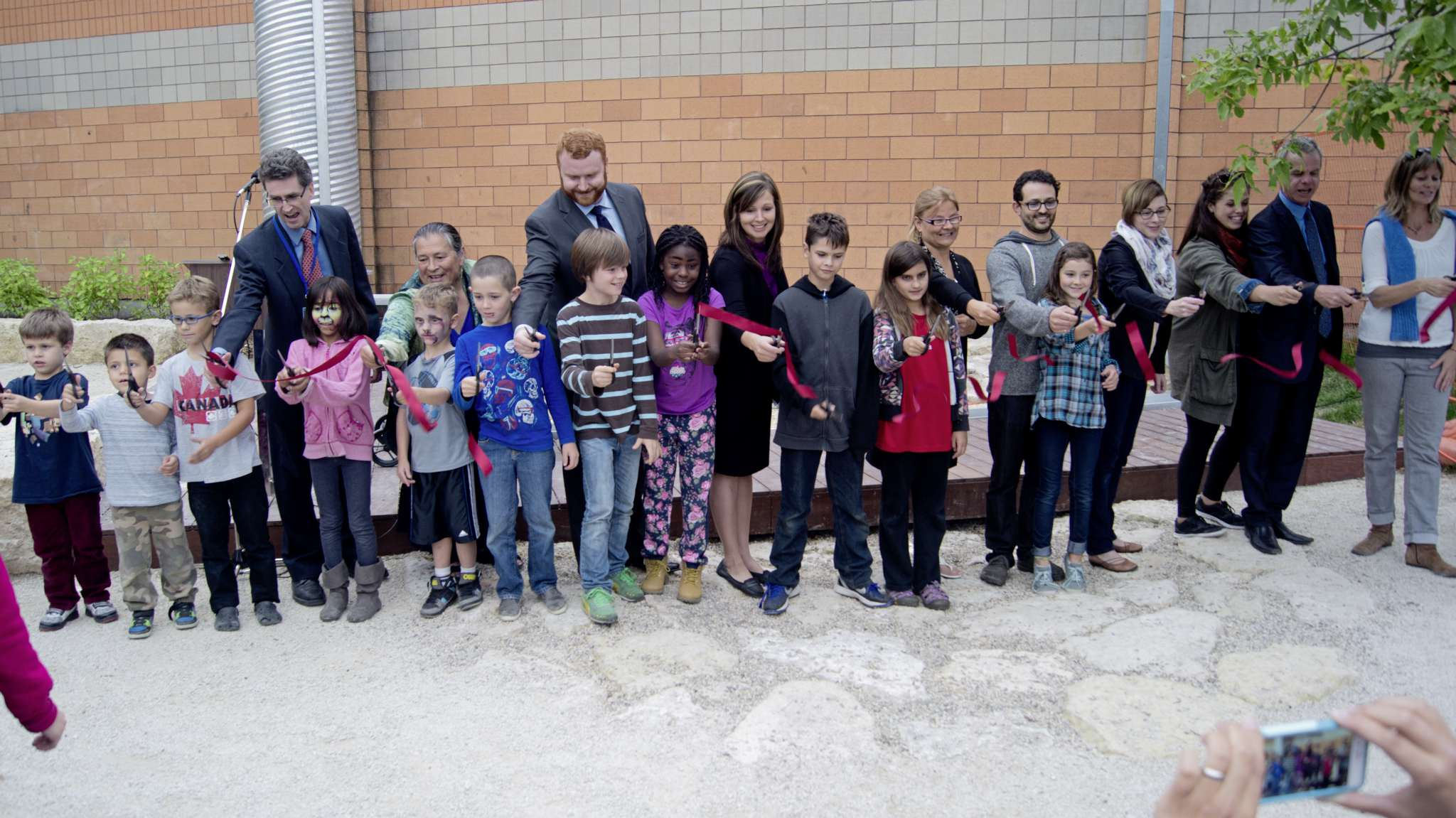 Students, staff, parents, education minister James Allum, Winnipeg city councillor Jenny Gerbasi's executive assistant, Hilary Allum, and Winnipeg School Division Board Trustee Chris Broughton cut the ribbon for the new Riverview outdoor learning space. DANIELLE DA SILVA - SOU