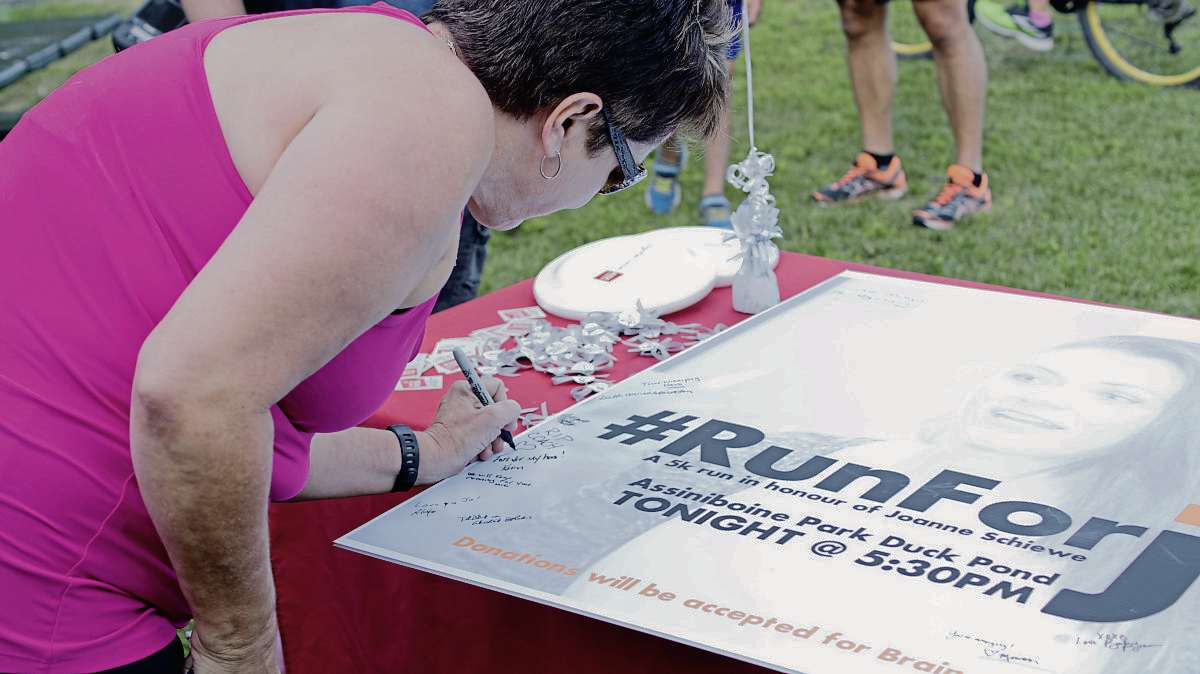 A runner signs a giant card at a memorial five-kilometre run held Aug. 30 in Assinniboine Park to celebrate the life of glioblastoma victim Joanne Schiewe. (Danielle Da Silva)