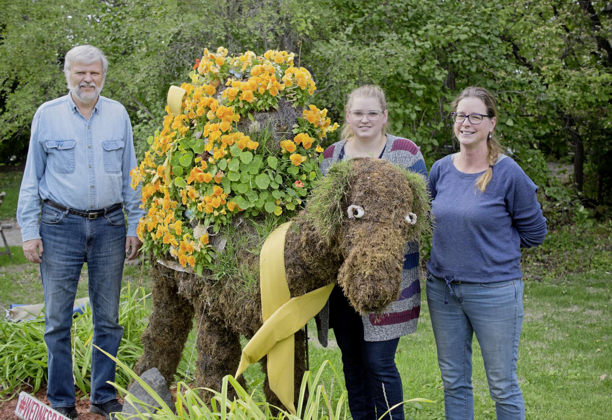 Wednesday the Camel, named after the hump in the work week, has become an icon in the Wellington Crescent neighbourhood for its deep closet of costumes and seasonal attire. The Stewart family is responsible for the ongoing horticulture and design project. Pictured from left is Paul, Zoe, and Dawn Stewart.