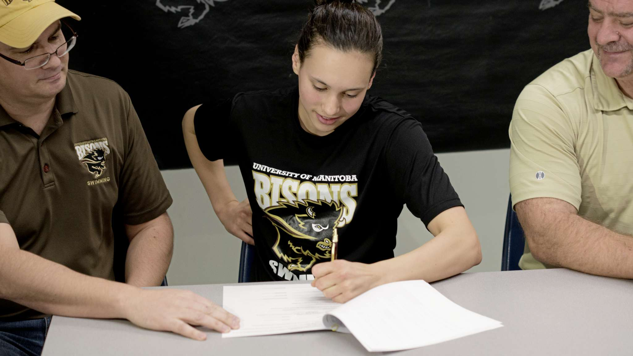 Kelsey Wog, 17, signs a contract with the University of Manitoba Bisons swim team on Dec. 8.