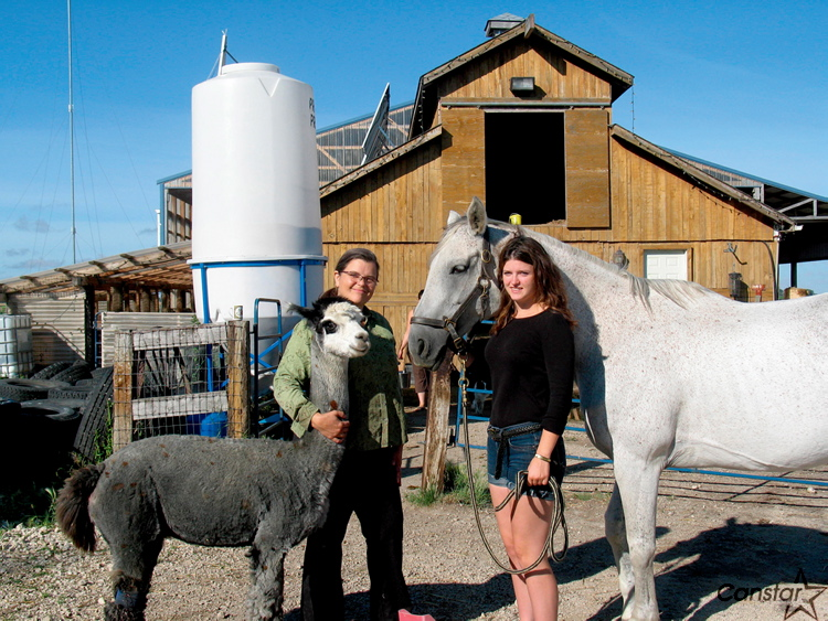 Louise May and her daughter, Zona, stand with some of their animals in front of the barn. Their farm will soon be host to more than 200 guests for the Manitoba Goddess Festival.