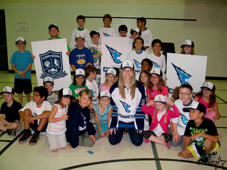Michaela Briscoe unveils the new Comets logo with a group of area youngsters.