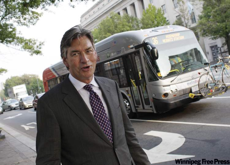 Former Manitoba premier Gary Doer admires a made-in-Winnipeg New Flyer bus as it passes near his office at the Canadian Embassy.