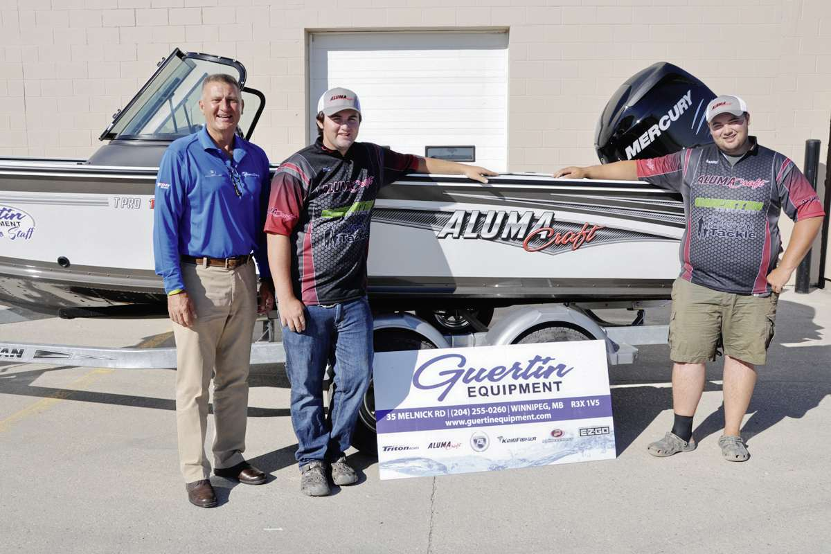 From left to right: Michael Guertin poses with Eric and Garret Barker and the boat Guertin Equipment is donating to the brothers' Cast 4 Kids efforts this year.