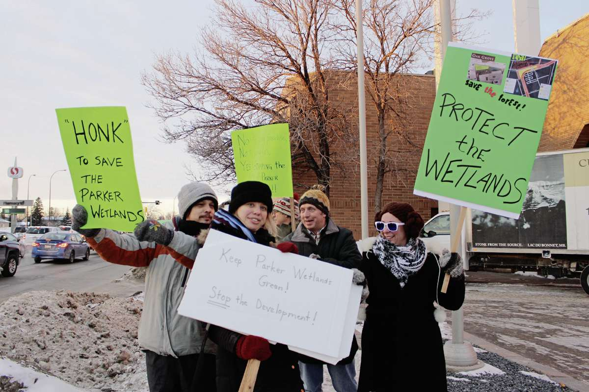 Protestors Derek Engen and Lisa Waldner were among the demonstrators who came out to a Feb. 10 open house to protest potential development of the Parker Wetlands. (Scott Billeck)